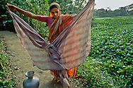 A folded sari can strain out dangerous bacteria, supplying safe drinking water for the family of this Bangladeshi woman. Such low-cost simple techniques can make a huge difference in local health conditions.