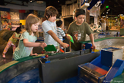 United States, Washington, Bellevue, KidsQuest Children's Museum, boys and girl building dam at Waterways exhibit