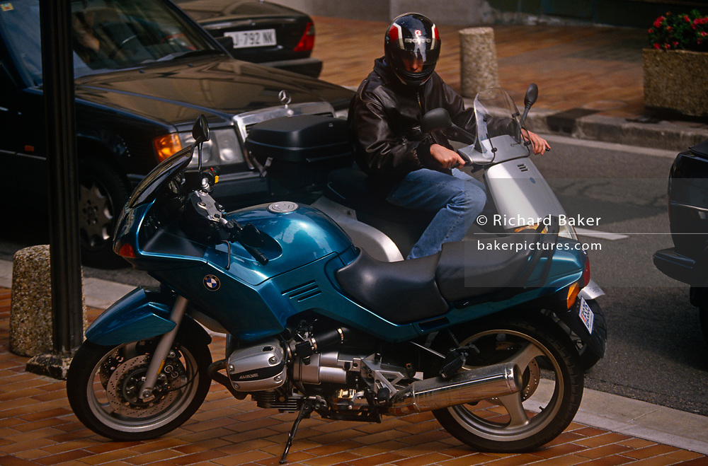 A scooter rider looks enviously at a better, larger, newer, more powerful, shiny blue BMW motorbike parked on the Monte Carlo pavement, on 13th April 1996, in Monaco.