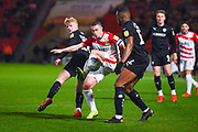 Tommy Rowe of Doncaster Rovers (10) in action between Ben Williams of Barnsley (28) and Dimitri Cavare of Barnsley (12) during the EFL Sky Bet League 1 match between Doncaster Rovers and Barnsley at the Keepmoat Stadium, Doncaster, England on 15 March 2019.