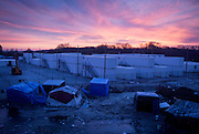 FRANCE, Calais: 18 January 2016 Tents and controversial shipping crates used to house some of the refugees in Calais sit in front of a purple sky at sunrise.  <br /> Teamed with an astonishing sunrise and ice cold conditions, it resembled a post  apocalyptic scene. A scene that an estimated 7,000 people have to live in.<br /> Rick Findler / Story Picture Agency