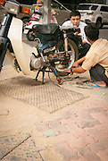 Roadside motorcycle mechanics are everywhere in central Saigon, Vietnam.