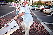 "Dec. 2, 2009 -- PHOENIX, AZ: GARRETT SMITH, from Phoenix, participates in a ""tug of war"" pitting health care against warfare in an intersection in Phoenix Wednesday. He was one of about 50 people from across the Phoenix metropolitan area who attended a protest and vigil against the troop increase President Barack Obama announced on Dec. 1. Photo by Jack Kurtz"