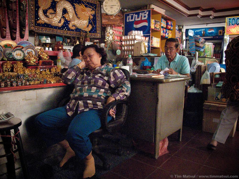 A woman sleeps in a souvenir shop at Wat Pho, Bangkok, Thailand.