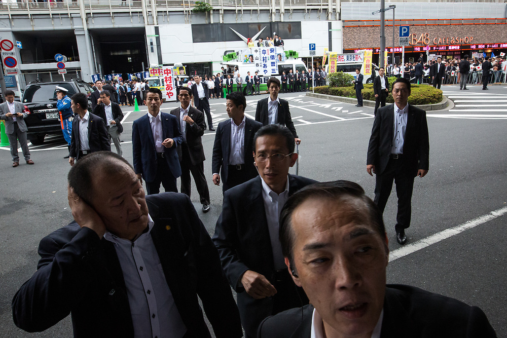 "TOKYO, JAPAN - JULY 1: Prime minister's security members were alerted when anti-Abe protesters suddenly gathers in front of an election campaign of main opposition, Liberal Democratic Party (LDP) in Akihabara, Tokyo, Japan on July 1, 2017. During the election campaign for Tokyo Metropolitan Assembly, anti-Abe protesters chant with their placards ""Abe wa Yamero!"" ""Resign Prime Minister Abe!"" during the campaign speech of PM Shinzo Abe for his candidate Aya Nakamura. (Photo: Richard Atrero de Guzman/NUR Photo)"