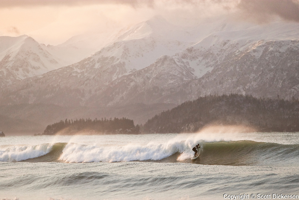 Don 'IceMan' McNamara surfing a winter swell at sunrise on Kachemak Bay, Alaska. The Kenai Mountains rise in the background.
