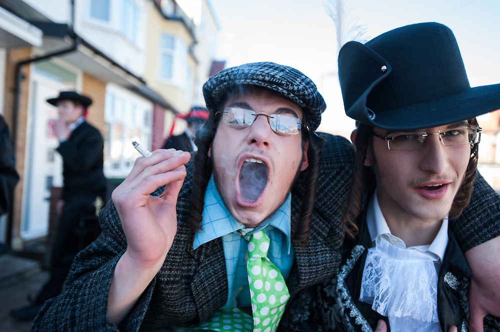London, UK - 16 March 2014: A young men from the Orthodox Jewish community of Stamford Hill smokes a cigarette during the festivity of Purim.