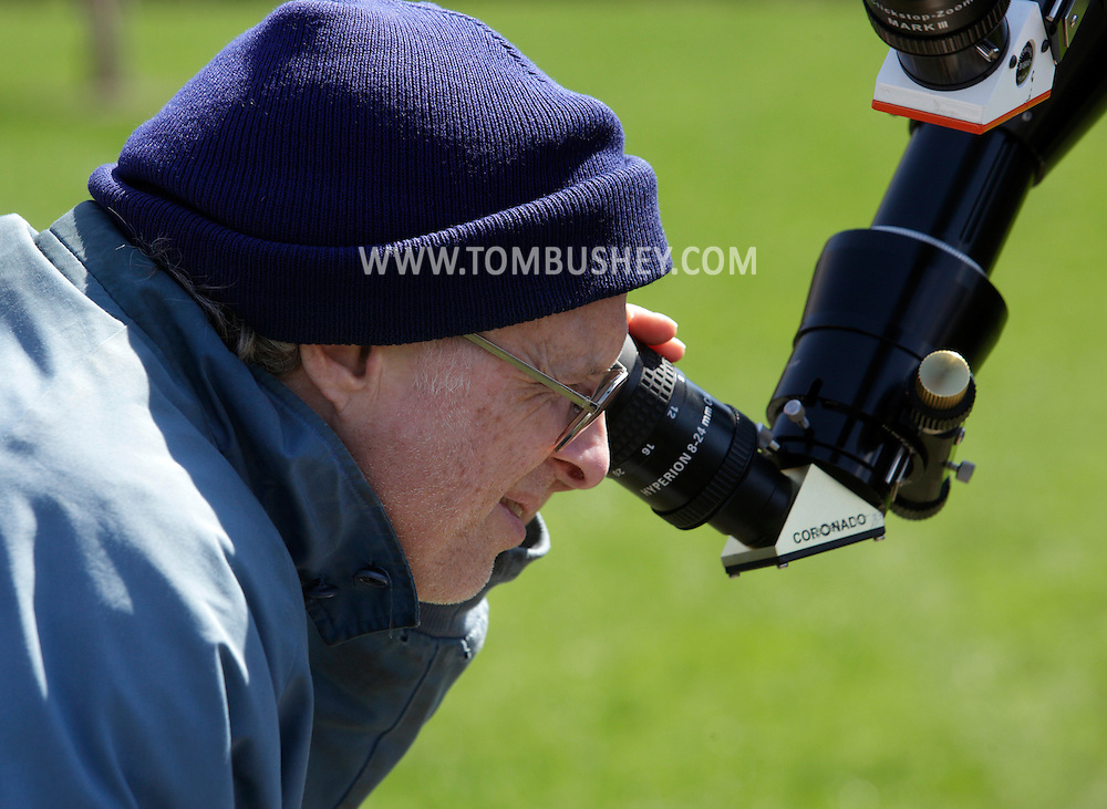 Suffern, New York - A man observes the sun through a filtered telescope during the Northeast Astronomy Forum and Telescope Show at Rockland Community College on April 17, 2011.