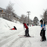 Locals ski down the road in Arawata Terrace, Fernhill, Queenstown, New Zealand after the biggest snow storm in New Zealand in the past 50 years. Queenstown, New Zealand, 15th August 2011. Photo Tim Clayton