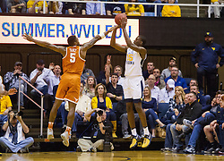 Feb 20, 2017; Morgantown, WV, USA; West Virginia Mountaineers forward Lamont West (15) shoots a three pointer over Texas Longhorns guard Kendal Yancy (5) during the first half at WVU Coliseum. Mandatory Credit: Ben Queen-USA TODAY Sports