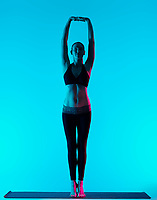 one caucasian woman exercising yoga exercices Tadasana mountain pose in silhouette studio isolated on blue background
