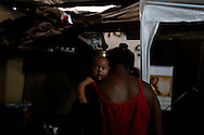 "A babysitter holds a baby at her makeshift home, part of the Nova Tuffy slum, in an abandoned factory in Rio de Janeiro, October 17, 2014. Since seven months ago, 1,800 families have been living inside the factory, which they occupied in March, with poor sanitation services and the fear of eviction. The occupants of the factory say they are not included in the housing program ""Minha Casa, Minha Vida"" (My House, My Life), and they would like to be included by the Brazilian government. The housing program is one of several government initiatives aimed at reducing poverty and social inequality that President Dilma Rousseff has held up as achievements of her administration as she campaigns for re-election. Photo/Pilar Olivares"