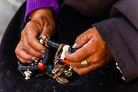 Tibetan woman holding her prayer beads, The Barkhor, Old Lhasa, Tibet (Xizang), China.