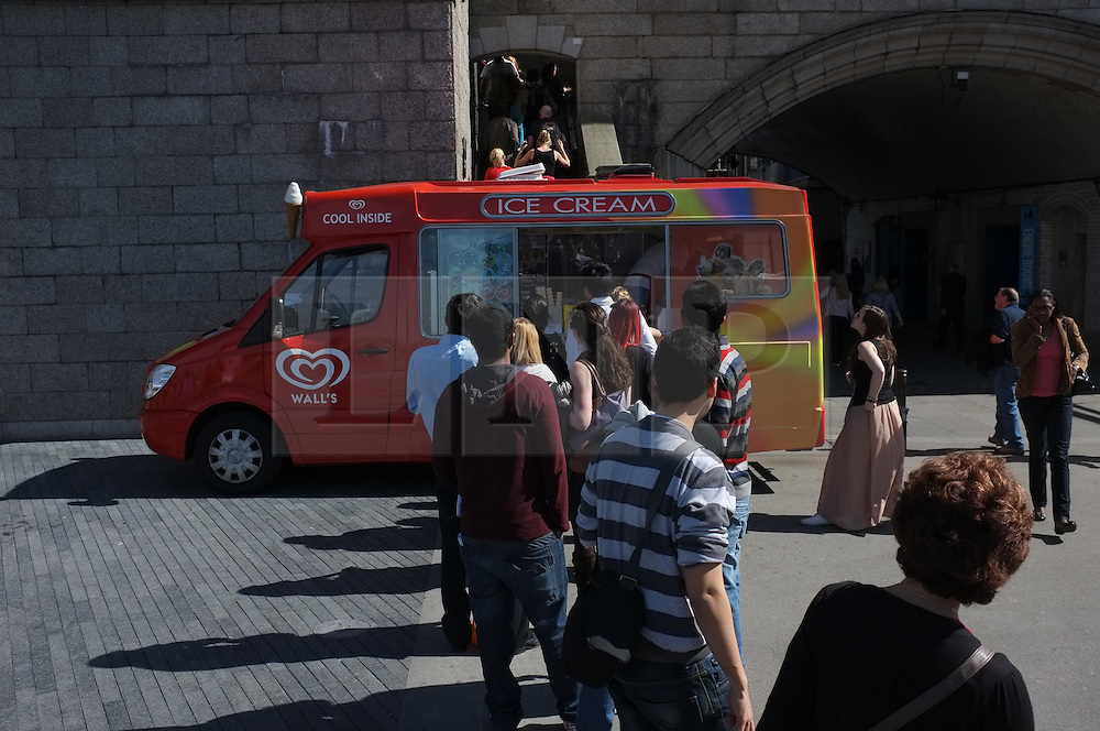 © LONDON NEWS PICTURES 2011. Photo by Paul Treacy. People gather at an ice cream van on the warmest day of the year so far in London.