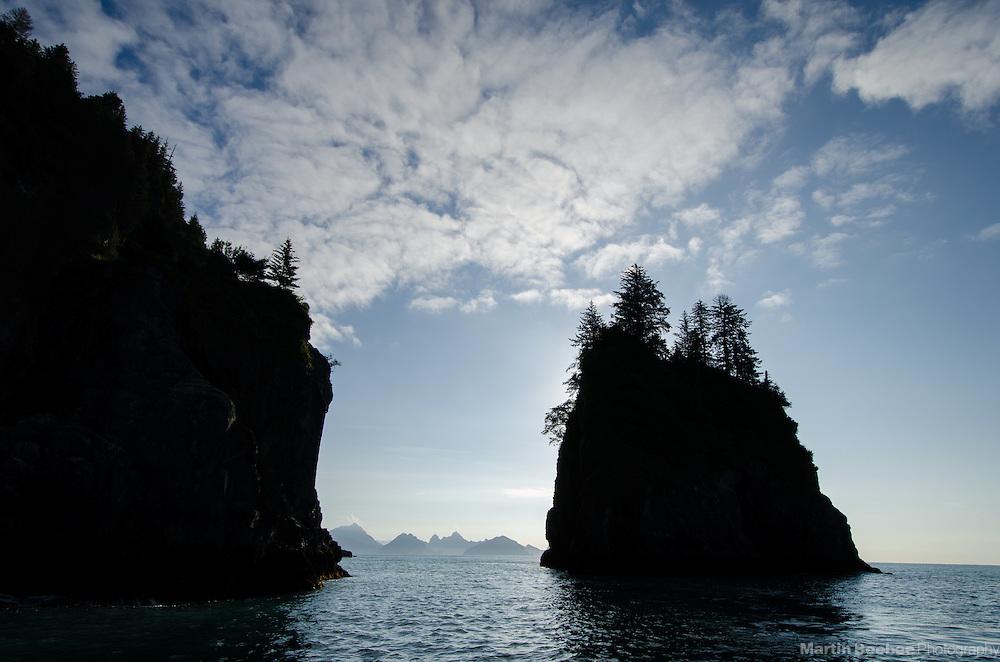 Silhouetted sea stacks and mountains, Kenai Fjords National Park, Alaska