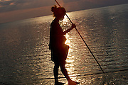 Woman collecting fish and sipu at sunset in Dili Christu Rei beach. @ Martine Perret. 9 juy 2009