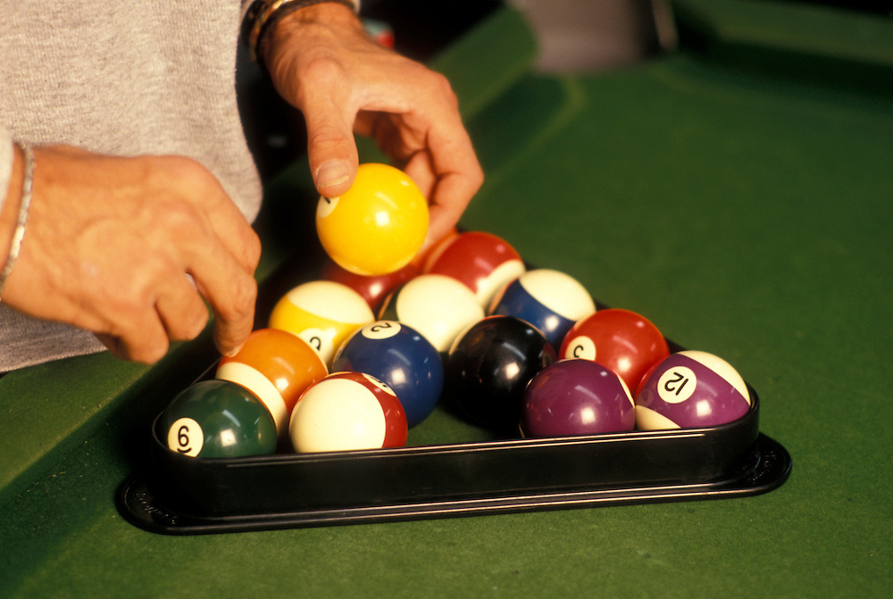 Canada, Manitoba, Winnipeg, Pool player arranges balls for break during game at Garry Billiards