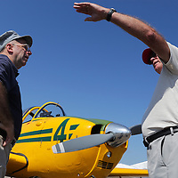 Maj. Mark Thoman, U.S.M.C.,Retired, left, and Col. Dave Gould, U.S.M.C.,Retired talk about learning the fly in the T-34, pictured in the background during Aviation Day Saturday October 11, 2014 at Wilmington International Airport in Wilmington, N.C. (Jason A. Frizzelle)