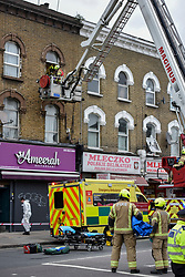 © Licensed to London News Pictures. 01/04/2020. London, UK. An aerial platform is used at an incident involving all emergency services a suspected COVID-19 case is isolatedand removed from home. Uxbridge Road in Shepherd's Bush was closed for an hour as ambulance, fire brigade and police attended, extracting the patient by crane from a three story apartment building in West London. PPE (personal protective equipment) was in evidence, with the fire brigade using full facerespirators normally reserved for firefighting. A police officercommented the Metropolitan police force are issued only with rubber gloves. Ambulance workers decontaminated the scene and reusable equipment before moving on.  Photo credit: Guilhem Baker/LNP