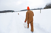 Flying J Farm owner Dick Jensen follows his 5-month old golden retriever Ruby as he carries water across his 250-acre organic farm near Johnstown, Ohio to feed chickens in their portable coop on Feb. 6, 2014. (Adam Cairns / The Columbus Dispatch)
