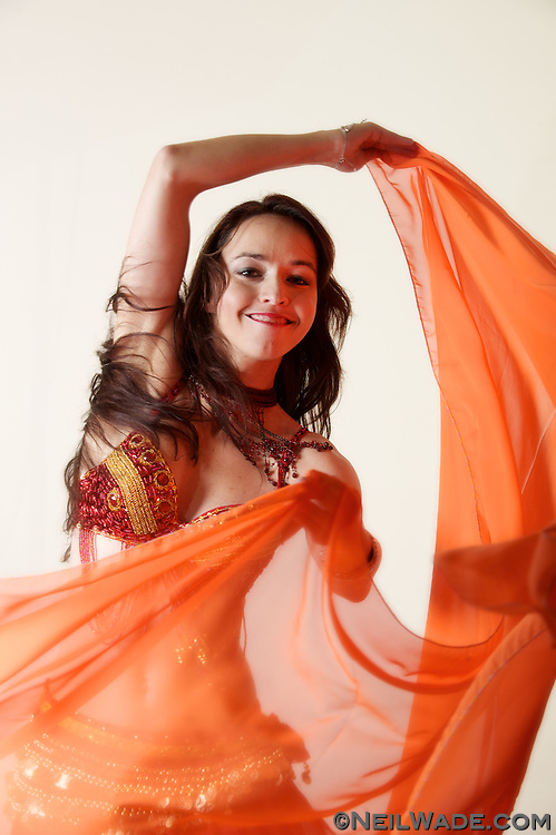 A belly dancer spins her scarf as she dances.