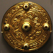 Escutcheons, gilt copper alloy.  600 Spelsbury and Standlake, Oxfordshire.  Jewelled disc brooch, silver, gold, glass gardet. 550-650, Faversham, Kent