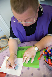 Day Service user with learning disability writing his name on a card,
