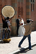 A wedding couple posing for a professional photographer in front of Notre Dame Cathedral.