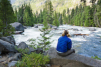Woman sitting beside the Icicle Creek in Icicle Canyon, Washington Cascades, USA.