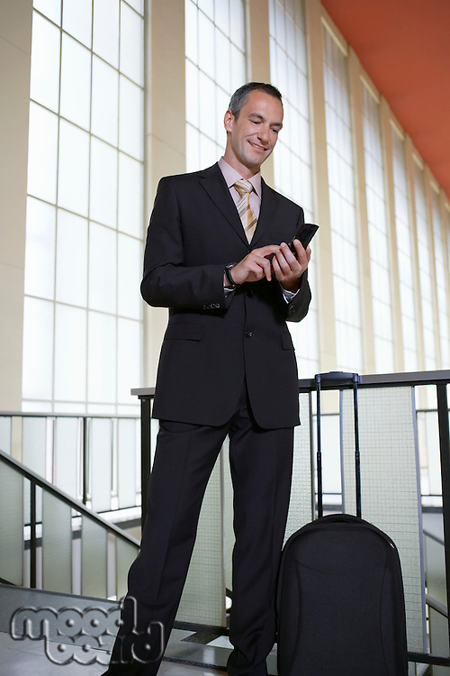 Business man sending text message in airport lobby