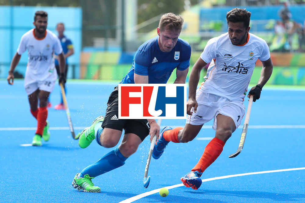 RIO DE JANEIRO, BRAZIL - AUGUST 09:  Lucas Rossi #27 of Argentina moves the ball past Harmanpreet Singh #1 of India during the hockey game on Day 4 of the Rio 2016 Olympic Games at the Olympic Hockey Centre on August 9, 2016 in Rio de Janeiro, Brazil.  (Photo by Christian Petersen/Getty Images)