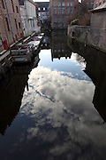 BRUGES, BELGIUM - FEBRUARY 06 : A general view of a canal on February 06, 2009 in Bruges, West Flanders, Belgium. The darkness of the narrow canal is contrasting with the light of the blue sky with white clouds reflected in the water. (Photo by Manuel Cohen)