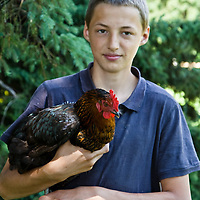 Ernst Pfenning a young farmer, holding one of his chickens.