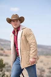 cowboy in a Winter coat outdoors on a mountain range