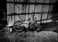 A children's bicycle left behind at farmhouse inside the 20 km (12.4 miles) nuclear no-entry zone during the hasty evacuation after the explosion at the Fukushima Daiichi Nuclear Power Plant.  Near Odaka, Fukushima Prefecture, Japan.  As of midnight 21 April 2011, the Japanese government declared the no-entry zone off-limits under the Disaster Countermeasures Basic Law which gives the police the power to detain anyone entering the zone for up to 30 days and impose a fine of up 100,000 JPY (US$1,200), which was exactly the risk necessary to take to make this photograph..