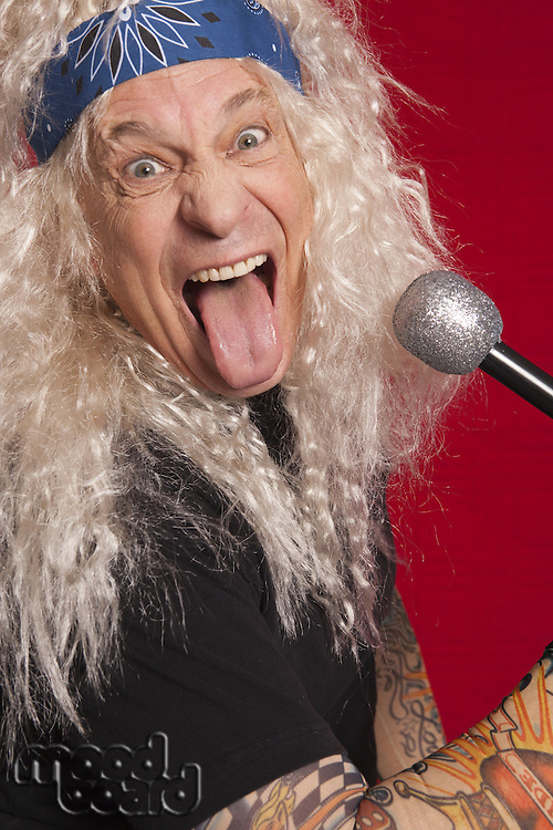 Close-up of senior musician making funny faces while singing over red background