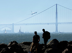 Spectators watch as a jumbo jet flies low over the Golden Gate Bridge while running through a demonstration of aerobatics during an air show over San Francisco Bay, Friday, Oct. 5, 2018 in San Francisco. The plane flew as part of the annual Fleet Week celebration. (Photo by D. Ross Cameron)