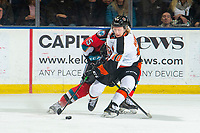KELOWNA, BC - NOVEMBER 8: Kobe Mohr #25 of the Kelowna Rockets back checks James Hamblin #10 of the Medicine Hat Tigers as he tries to gain control of the puck at Prospera Place on November 8, 2019 in Kelowna, Canada. (Photo by Marissa Baecker/Shoot the Breeze)