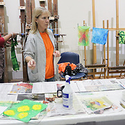 """Althea Johnson, left, hangs a quilt square to dry as Mary Bryan talks to instructor September Krueger(out of frame) during """"Create Your Own Quilt Squares"""" Sunday November 23, 2014 at the Cameron Art Museum in Wilmington, N.C. (Jason A. Frizzelle)"""