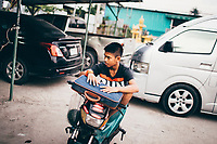 Preeda Samrong waits for his younger brother before a Muay Thai fight in Rayong, Thailand.