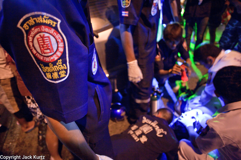 "02 OCTOBER 2009 -- BANGKOK, THAILAND: Volunteers from the Poh Teck Tung Foundation try to help a man who was involved in a motorcycle accident. The man died at the scene. The 1,000 plus volunteers of the Poh Teck Tung Foundation are really Bangkok's first responders. Famous because they pick up the dead bodies after murders, traffic accidents, suicides and other unplanned, often violent deaths, they really do much more. Their medics respond to medical emergencies, from minor bumps and scrapes to major trauma. Their technicians respond to building collapses and traffic accidents with heavy equipment and the ""Jaws of Life"" and their divers respond to accidents in the rivers and khlongs of Bangkok. The organization was founded by Chinese immigrants in Bangkok in 1909. Their efforts include a hospital, college tuition for the poor and tsunami relief.   PHOTO BY JACK KURTZ"