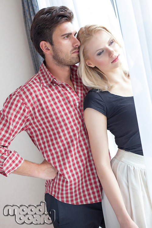 Thoughtful young couple at hotel window