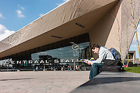 Man sits in front of the new Rotterdam central station which has been redeveloped to represent the transportation hub's important role in the city and as part of the european train network. A collaboration of  benthem crouwel architects, MVSA architects and west 8 architects.