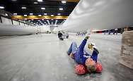 Gary Johnson checks the paint on a wind turbine blade at TPI Composites in Newton, Iowa on February 12, 2010.