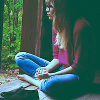 Young, slender, caucasian looking woman with blonde hair wearing glasses. She is sitting alone inside an abandoned cabin in the woods and looking out the open doorway with her hand and feet neatly crossed and folded. Her shoes are placed together in front of her.