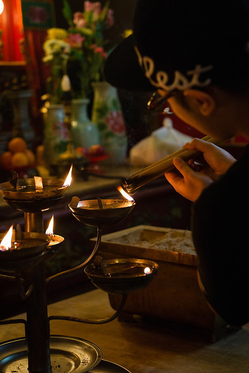 Worshiper lighting incense candles at Man Mo Temple