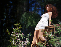 Young woman in a white summer dress sitting on the edge of balcony railings in a green garden enjoying sunshine in spring