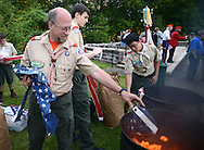 CHURCHVILLE, PA - JUNE 14: Assistant Scout Master Mike Dabenko of Boy Scout Troop 5 of Churchville tosses the star portion of an American flag into a separate fire to properly dispose of American flags during a ceremony June 14, 2014 at Northampton Township Municipal Park in Churchville, Pennsylvania. The Northampton supervisors and Veterans Advisory Committee held the ceremony in which people brought their old or tattered American flags for proper disposal.  (Photo by William Thomas Cain/Cain Images)