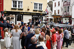 © Licensed to London News Pictures. 11/05/2018. WINDSOR, UK.  A happy bride and groom are showered with confetti after being married at St John the Baptist church in Windsor.  Preparations continue in the town centre for the upcoming wedding between Prince Harry and Meghan Markle on 19 May.  Thousands of people are expected to visit the town for what has been billed as the wedding of the year.  Photo credit: Stephen Chung/LNP