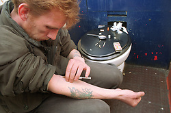 Homeless man injecting himself with heroin in toilet,